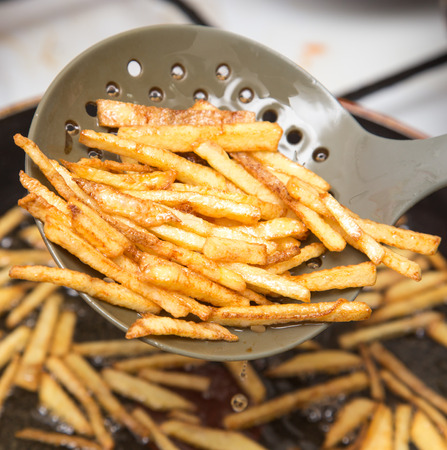 cooking potato fries in oil Stock Photo