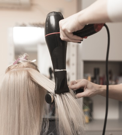Styling female hair dryer in the beauty salon Stock Photo