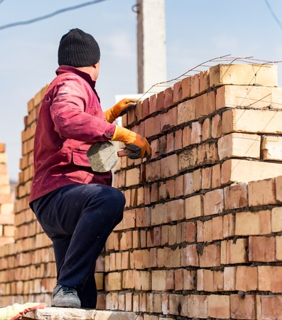 Worker builds a brick wall in the house . Stock Photo