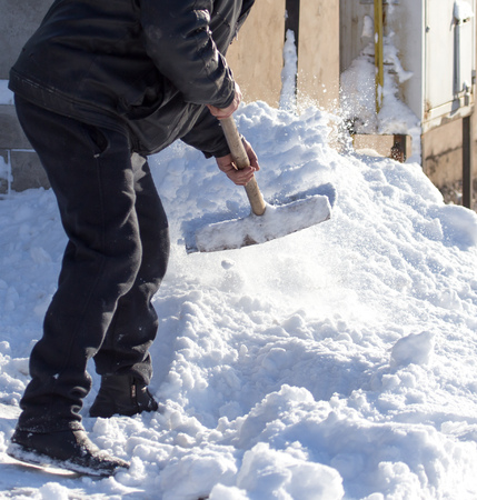 Worker removes snow from the road in nature