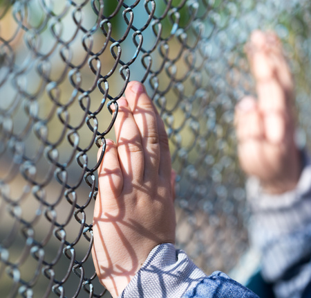 Childs hand on a grid of a metal fence . Stock Photo