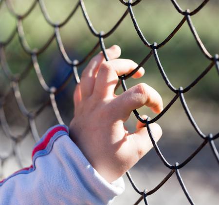 De hand van het kind op een net van een metaalomheining.