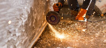Worker cuts a metal pipe with sparks .