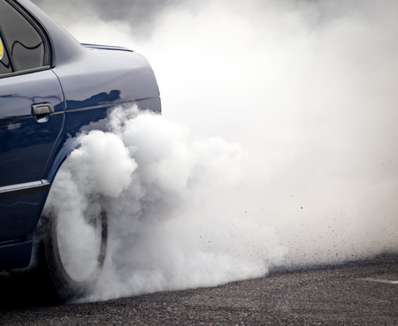 burnout: Smoke from under the wheels of the car .