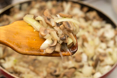 Mushrooms with onions are fried in a frying pan . Stock Photo