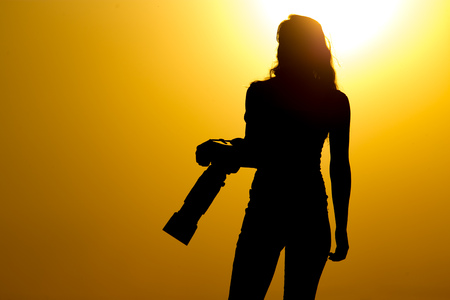 daybreak: Silhouette of a girl photographer at sunset .