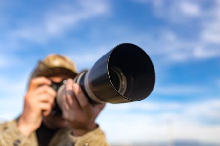 カメラマンは、大規模なレンズで写真を取る。