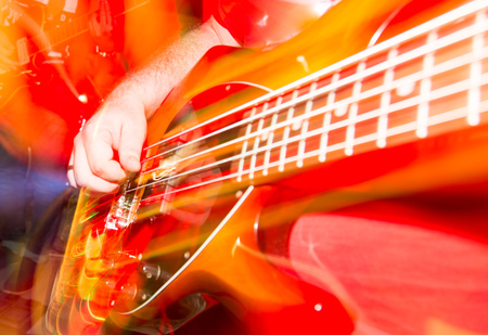 Musician playing guitar in a rock band . Stock Photo