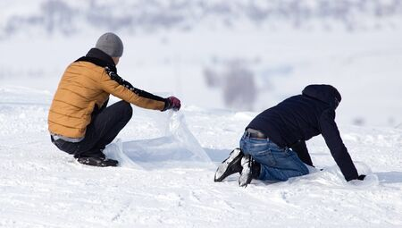 Man rolls down the hill in winter .