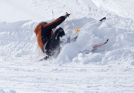 The skier fell in the snow at speed .