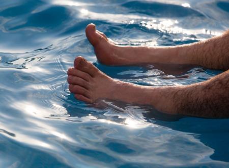 Benen van mannen dichtbij het zwembad op vakantie