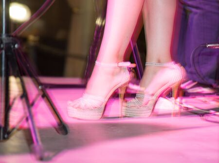 Feet of a girl on stilettos on stage . Stock Photo