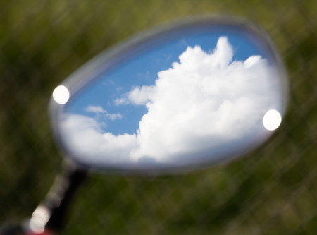motobike: Reflection of clouds on a blue sky in a motobike mirror .