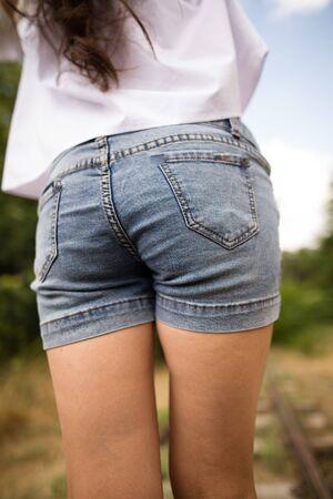 Booty girl in denim shorts in the park . Stock Photo