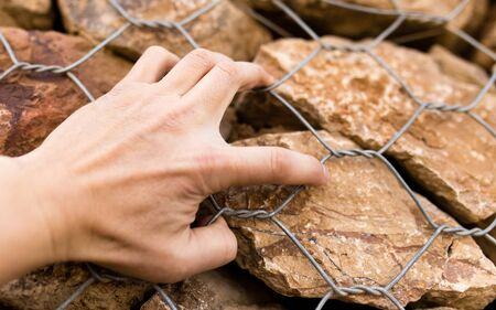 Mans hand on a stone wall Stock Photo