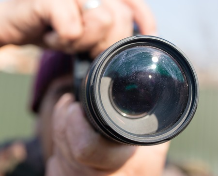 A large lens in the camera of a man