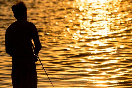 Fisherman with a fishing rod at sunset