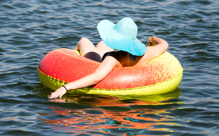 The girl is floating on a tank on the lake