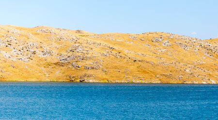 Blue lake near yellow rocks in nature Stock Photo