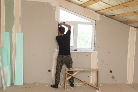 The worker works with plastic for windows in the house Stock Photo