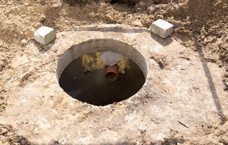 Een open betonnen drainage luik in de buurt van het huis