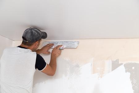 Il lavoratore si blocca il mortaio sul muro Archivio Fotografico