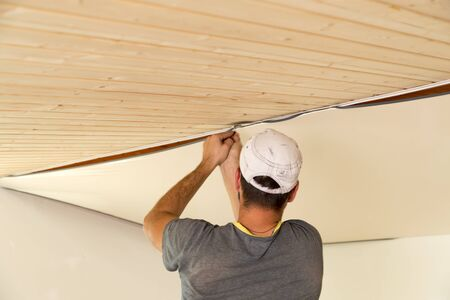 Workers stretch the stretch ceiling in the room Stock Photo