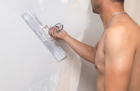 plasterer: the worker plastered the mortar on the wall . Stock Photo