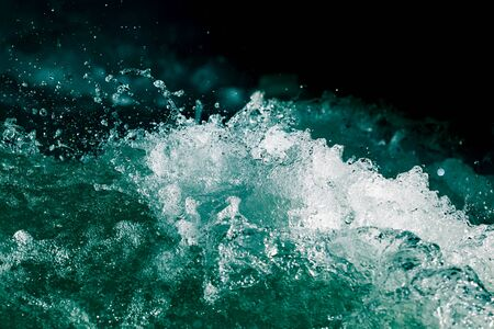 Splash of stormy water in the ocean on a black background .