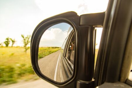side mirror on the car on the road .