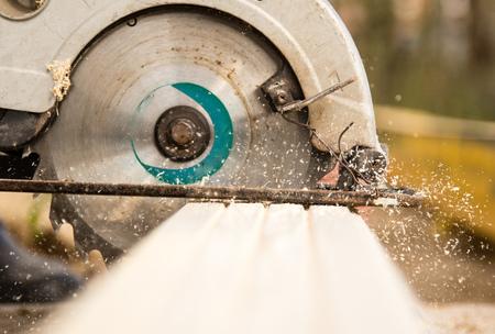 werknemer zaagt een houten plank op een bouwplaats.