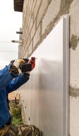 The worker insulates the house from foam plastic .