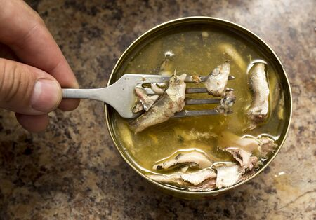 Open fish preserves and fish on the fork . Stock Photo