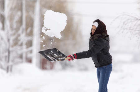 Girl with a shovel cleans the snow Stock Photo
