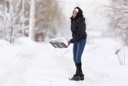 Girl with a shovel cleans the snow . Standard-Bild