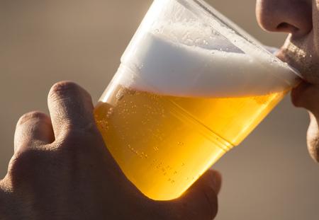 手にプラスチックカップの新鮮なビール.