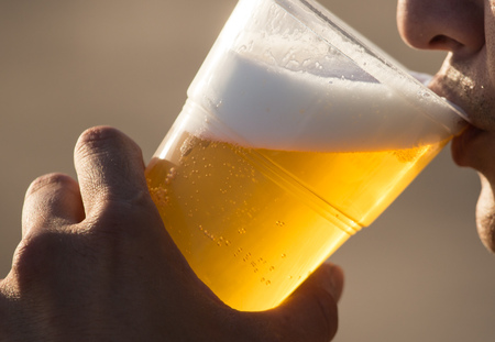 Fresh beer in a plastic cup in the hand .