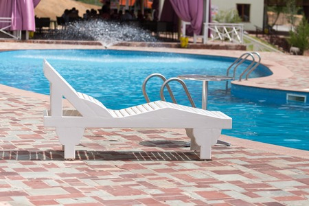 white sunbeds by the pool in the open air .