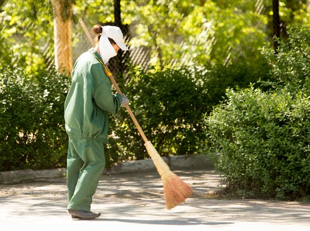 Janitor with a broom in the park .