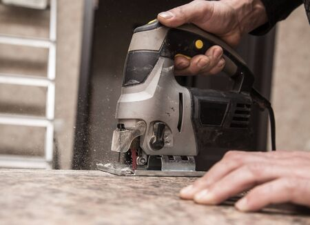 Master cuts wood with a jig saw . Stock Photo