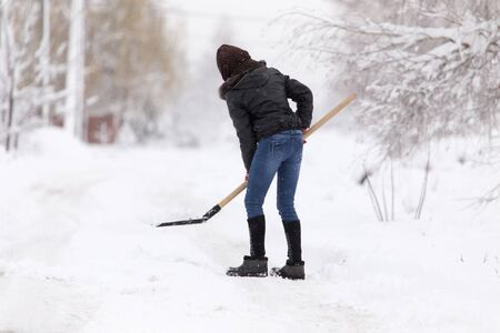 Girl with a shovel cleans the snow . Stock Photo
