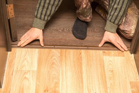 Een man maakt een drempel op de vloer. Stockfoto - 94262333