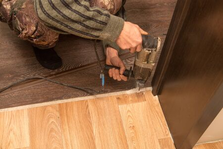 A man is making a threshold on the floor . Stockfoto - 95503399