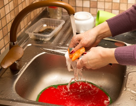 Washing dishes in the water under the tap .