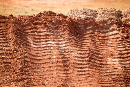 Traces from the car on the red clay soil .