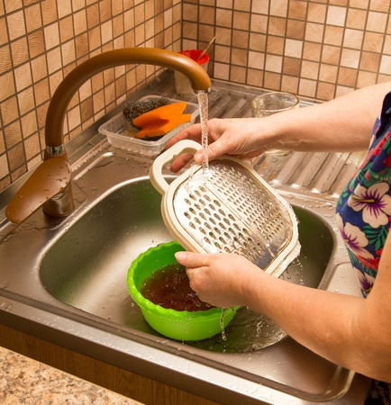 Washing dishes in the water under the tap