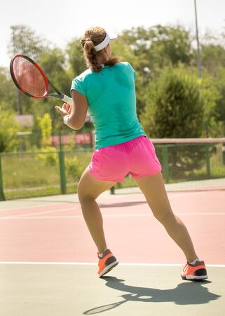 Girl playing with a racket in tennis on the court .