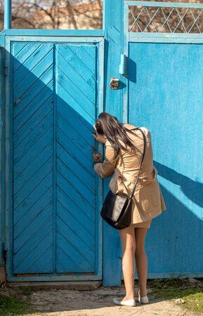 The girl opens the door in the metal gate . Stock Photo