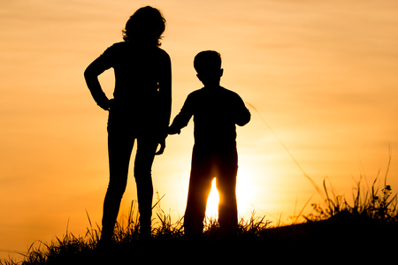Silhouette of Mom and son in the rays of sunset .