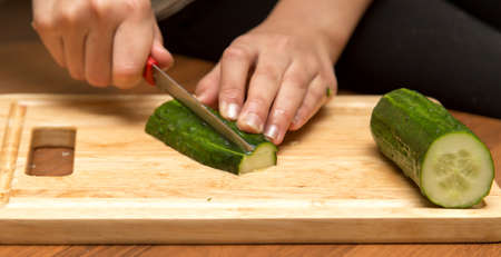 Slicing cucumber with a knife on the board Stock Photo